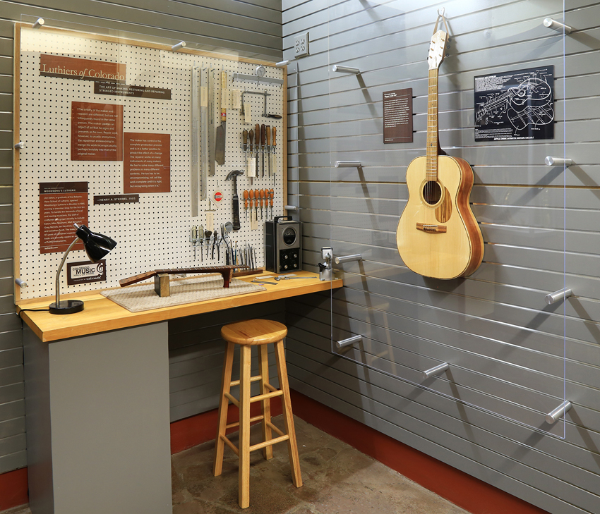 lutherie workshop showing process of stringing with finished acoustic guitar hanging